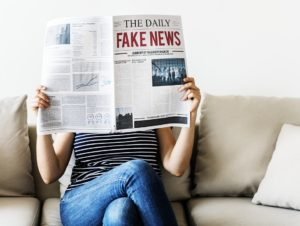 persona legge giornale con titolo the daily fake news