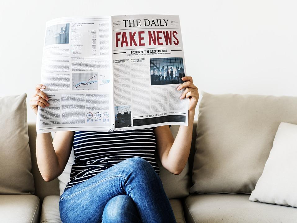 persona legge giornale con titolo the daily fake news