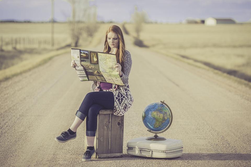 ragazza in viaggio con mappa e mappamondo