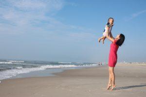 donna al mare con bambino piccolo