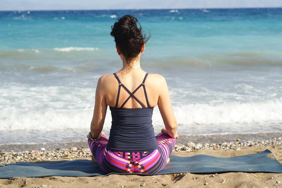 donna che fa yoga al mare